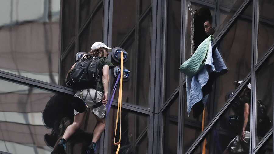 A man attempting to scale Trump Tower talks with a New York Police officer through a window that was broken out by police Wednesday, Aug. 10, 2016, in New York.