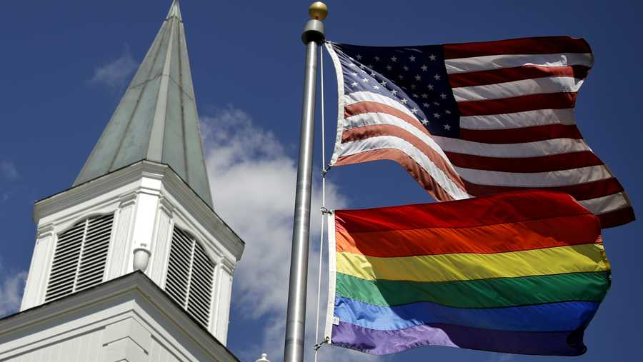 In this April 19, 2019 file photo, a gay pride rainbow flag flies along with the U.S. flag in front of the Asbury United Methodist Church in Prairie Village, Kan.