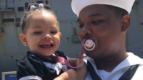 Young girl welcomes home Navy father