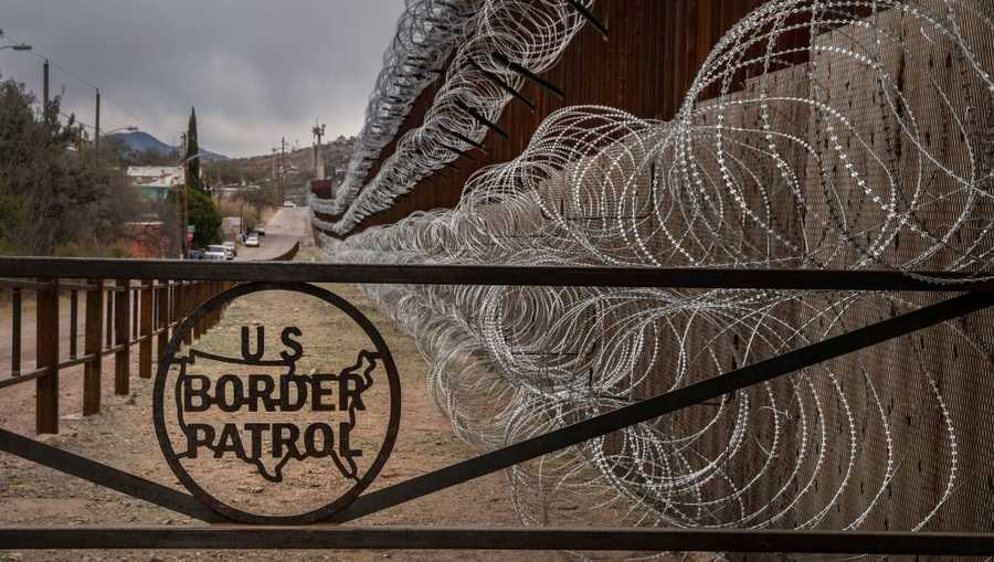 A metal fence marked with the US Border Patrol sign prevents people to get close to the barbed/concertina wire covering the U.S./Mexico border fence, in Nogales, Arizona, on Feb. 9, 2019.